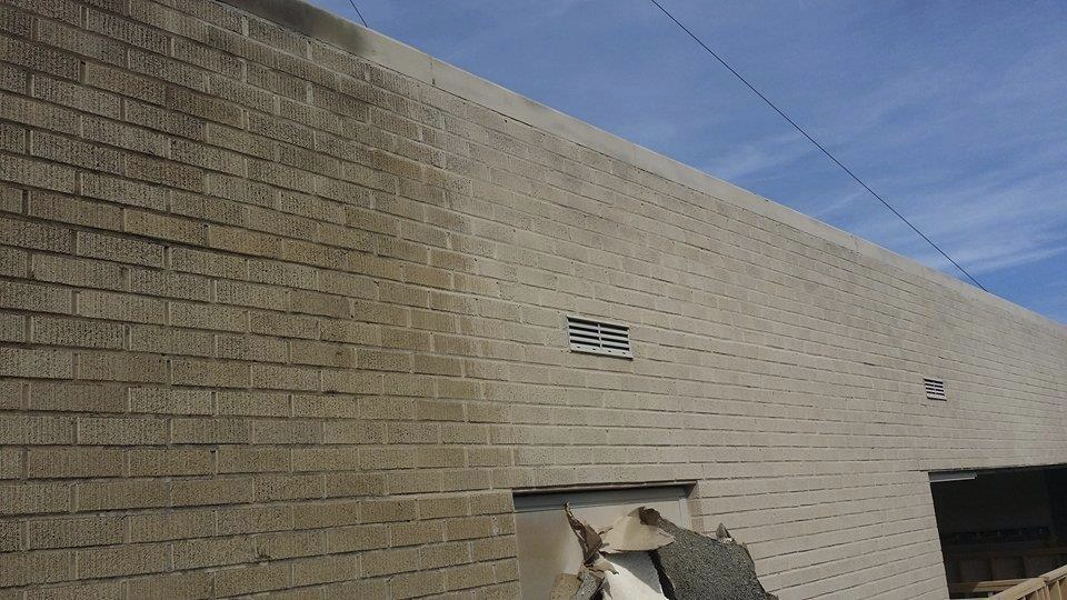 Mobile blasting at work on an 80-year-old brick building exterior